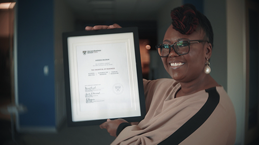 A learner displaying their certificate of completion from a HBS Online course.